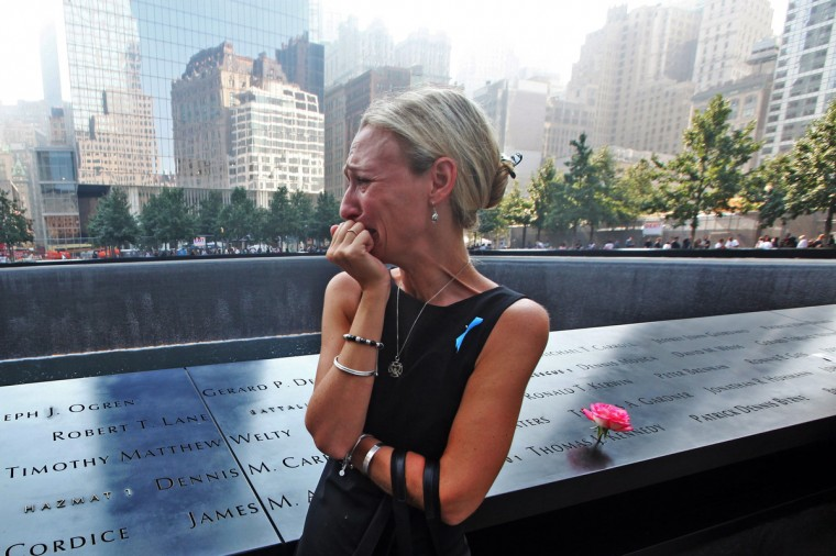 Carrie Bergonia of Pennsylvania looks over the name of her fiance, firefighter Joseph Ogren at the 9/11 Memorial during ceremonies for the twelfth anniversary of the terrorist attacks on lower Manhattan at the World Trade Center site on September 11, 2013 in New York City. The nation is commemorating the anniversary of the 2001 attacks which resulted in the deaths of nearly 3,000 people after two hijacked planes crashed into the World Trade Center, one into the Pentagon in Arlington, Virginia and one crash landed in Shanksville, Pennsylvania. Following the attacks in New York, the former location of the Twin Towers has been turned into the National September 11 Memorial & Museum. (Chris Pedota/Getty Images)