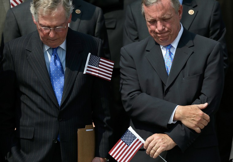 Senate Minority Leader Mitch McConnell (R-KY) and Senate Majority Whip Richard Durbin (D-IL) bow their heads in prayer during a September 11th remembrance ceremony on the steps of the U.S. Capitol September 11, 2013 in Washington, DC. (Win McNamee/Getty Images)