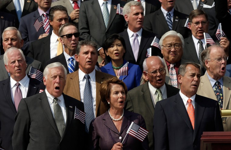 "(L-R) Rep. Steny Hoyer (D-MD), House Minority Leader Nancy Pelosi (D-CA), and Speaker of the House John Boehner (R-OH) wave American flags along with other members of Congress as they sing ""God Bless America"" during a September 11th remembrance ceremony on the steps of the U.S. Capitol September 11, 2013 in Washington, DC. (Win McNamee/Getty Images)"