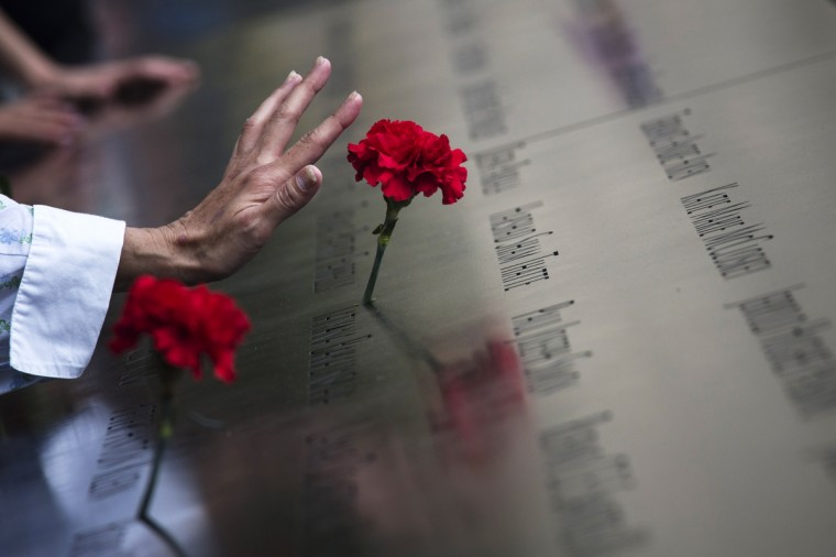 A woman touches a carnation left on a name inscribed into the North Pool during 9/11 Memorial ceremonies marking the 12th anniversary of the 9/11 attacks on the World Trade Center in New York on September 11, 2013 in New York City. (Adrees Latif/Reuters)