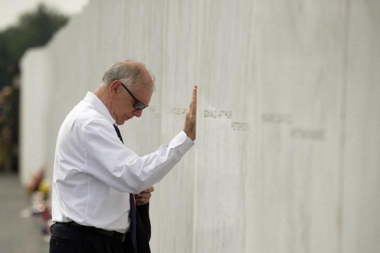 Patrick White, a relative of crash victim Louis Nacke, pauses at his name at the Flight 93 National Memorial during ceremonies commemorating the 12th anniversary of the 9/11 attacks on September 11, 2013 in Shanksville, Pennsylvania. (Jeff Swensen/Getty Images)