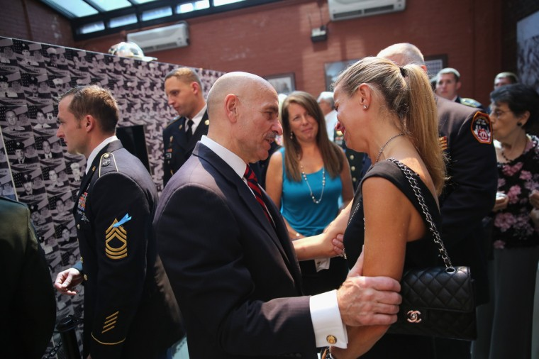 "New York City Fire Commissioner Salvatore Cassano comforts Hope McHale at a ceremony commemorating the 12th anniversary of 9/11 attacks on September 11, 2013 in New York City. McHale's husband, fire marshal Martin ""Woodie"" McHale survived the collapse of the World Trade Center but died Christmas Eve 2012 of a heart attack. (John Moore/Getty Images)"