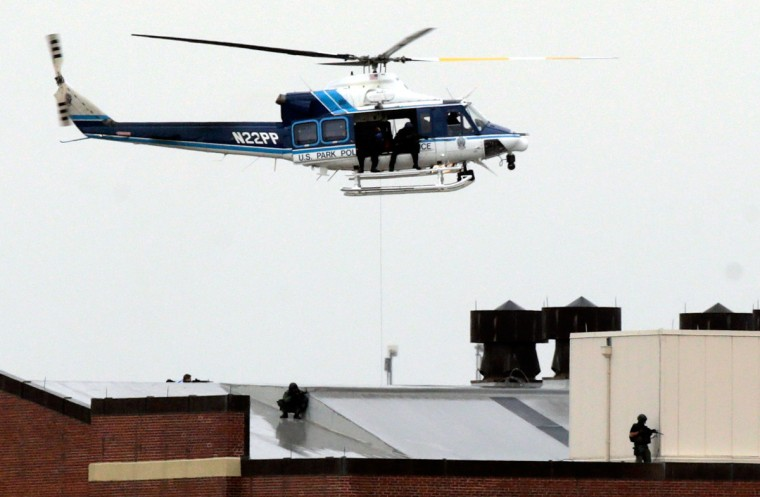 A Park Police helicopter hovers above snipers on the roof of a building at the Navy Yard complex where a shooting took place early this morning September 16, 2013 in Washington, DC. Early reports indicate that several people may have been shot, and police are still trying to determine the number of suspects involved in the shooting. (Win McNamee/Getty Images)