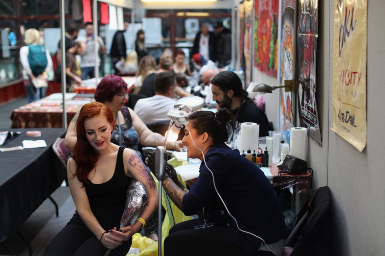 Body art enthusiasts receive tattoos at the London Tattoo Convention in Tobacco Dock on September 27, 2013 in London, England. (Oli Scarff/Getty Images)