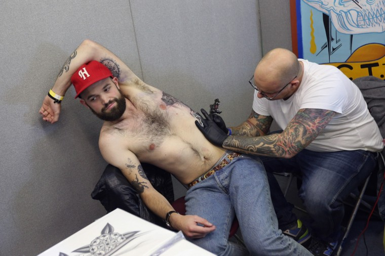 A tattoo enthusiast has his side tattooed at the London Tattoo Convention in Tobacco Dock on September 27, 2013 in London, England. (Oli Scarff/Getty Images)