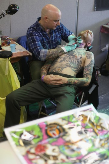 A tattoo enthusiast has his neck tattooed at the London Tattoo Convention in Tobacco Dock on September 27, 2013 in London, England. (Oli Scarff/Getty Images)