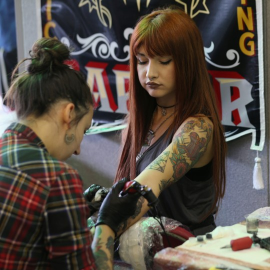 A tattoo enthusiast has her arm tattooed at the London Tattoo Convention in Tobacco Dock on September 27, 2013 in London, England. (Oli Scarff/Getty Images)