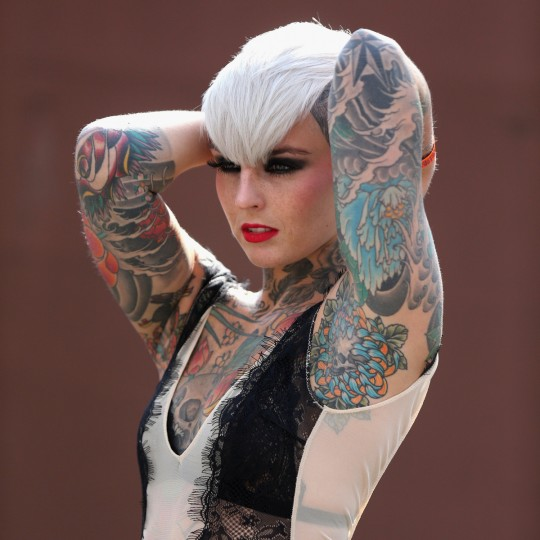 A tattooed model poses for photographers at the London Tattoo Convention in Tobacco Dock on September 27, 2013 in London, England. (Oli Scarff/Getty Images)