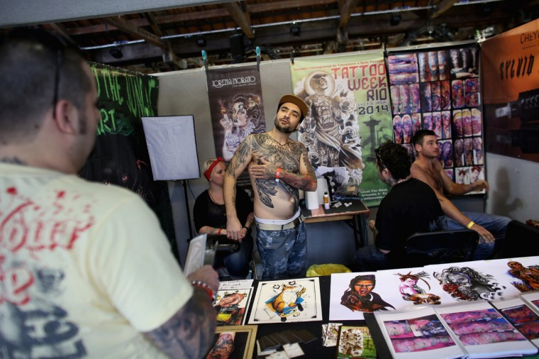 Tattoo artists prepare their stand at the London Tattoo Convention in Tobacco Dock on September 27, 2013 in London, England. (Oli Scarff/Getty Images)