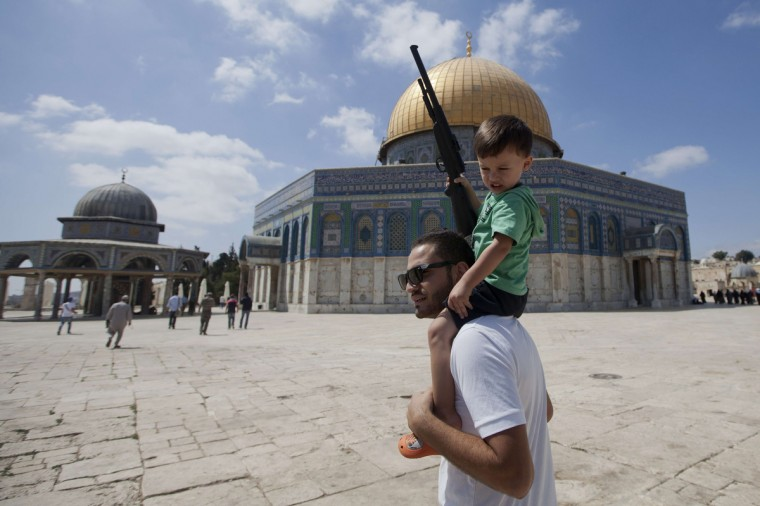 A Palestinian man carries on his shoulders a child holding a fake gun outside the Dome of Rock at the Al-Aqsa Mosque compound, Islam's third most holy site after disturbances that caused the temporary closure to the access of the Mosque. The entrance to Al-Aqsa Mosque in Jerusalem's old city was temporary closed after the arrest of a firebrand Arab-Israeli Islamist preacher the day before. (Ahmad Gharabli/Getty Images)
