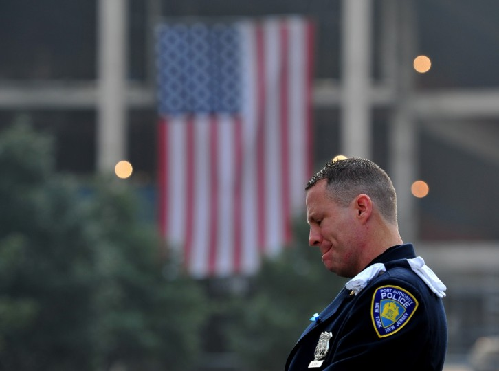 Daniel Henry, a Port Authority of New York/New Jersey police officer, pauses during a moment of silence at 9:01 am EDT, at the South reflecting pool at the 9/11 Memorial during ceremonies marking the 12th anniversary of the 9/11 attacks on the World Trade Center in New York, September 11, 2013. (Stan Honda/Getty Images)