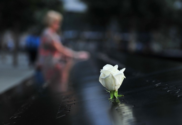 A woman pauses at the South reflecting pool at the 9/11 Memorial during ceremonies marking the 12th anniversary of the 9/11 attacks on the World Trade Center in New York, September 11, 2013. (Stan Honda/Getty Images)