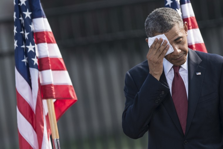 US President Barack Obama wipes sweat during a memorial service at the National 9/11 Pentagon Memorial September 11, 2013 in Washington, DC. Obama attended the event to mark the 12th anniversary of terrorist attacks on the Pentagon and the World Trade Center. (Brendan Smialowski/Getty Images)