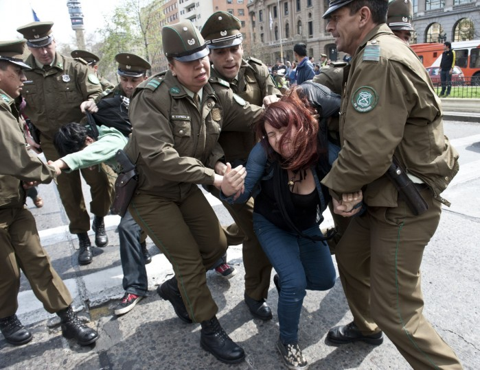 Chilean police arrest a demonstrator taking part in a protest along Alameda avenue in Santiago during the commemoration of the 40th anniversary of the military coup led by General Augusto Pinochet that deposed him. (Claudio Santana/Getty Images)