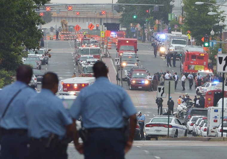 A general view shows police and first responder activity on M Street, SE near the Washington Navy Yard on September 16, 2013 in Washington, DC. An unidentified gunman opened fire at the US Navy Yard in Washington on Monday and wounded several people including two police officers, officials reported. Police and FBI agents descended on the area in force as helicopters buzzed overhead, amid reports the shooter was armed with an assault rifle and was on the loose in the complex. A Washington DC police officer and another law enforcement officer had been shot while the gunman had allegedly barricaded himself in a room in a headquarters building, the Washington Post and other media reported. At one point a police helicopter hovering over the complex lowered a man down by rope into the compound. Police blocked off intersections around the Navy Yard as military troops in uniform stood guard at street corners.(Mandel Ngan/Getty Images)
