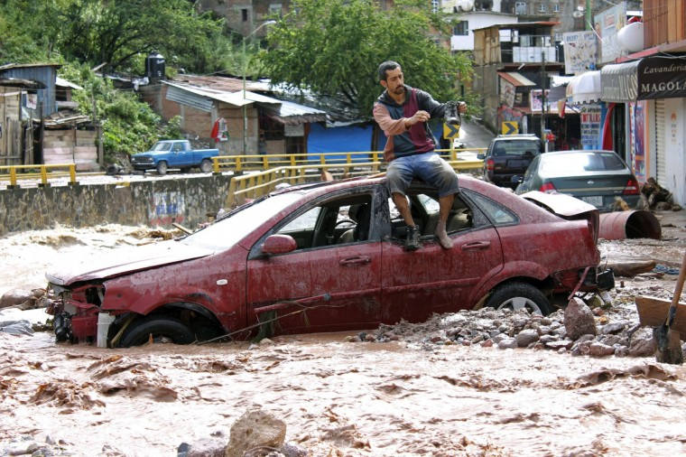 A man sits atop a car while trying to cross a flooded street in Chilpancingo, state of Guerrero, Mexico. Mexican authorities scrambled Tuesday to launch an air lift to evacuate tens of thousands of tourists stranded amid floods in the resort of Acapulco following a pair of deadly storms. The official death toll rose to 47 after the tropical storms, Ingrid and Manuel, swarmed large swaths of the country during a three-day holiday weekend, sparking landslides and causing rivers to overflow in several states. (Edurado Guerrero/Getty Images)