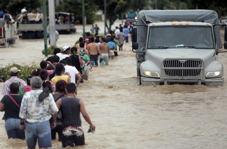 Residents and tourists wade through a flooded street in Acapulco, Guerrero state, Mexico as heavy rains hit the country. Mexican authorities scrambled Tuesday to launch an air lift to evacuate tens of thousands of tourists stranded amid floods in the resort of Acapulco following a pair of deadly storms. The official death toll rose to 47 after the tropical storms, Ingrid and Manuel, swarmed large swaths of the country during a three-day holiday weekend, sparking landslides and causing rivers to overflow in several states. (Pedro Pardo/Getty Images)