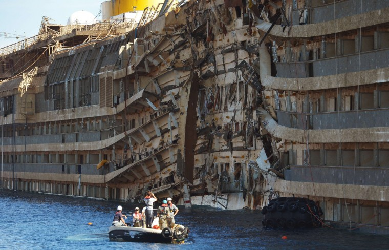 Members of the US salvage company Titan and Italian firm Micoperi inspect the wreck of Italy's Costa Concordia cruise ship after emerging from water, near the harbor of Giglio Porto. Salvage operators in Italy lifted the Costa Concordia cruise ship upright from its watery grave off the island of Giglio in the biggest ever project of its kind. The ship was upright for the first time since the January 13, 2012 tragedy, and led to applause and cheers in the port, in a dramatic climax to the massive salvage operation. Local residents and survivors spoke of an eerie feeling as the ship rose, saying the sight reminded them of the tragedy that claimed 32 lives. (Vincenzo Pinto/Getty Images)