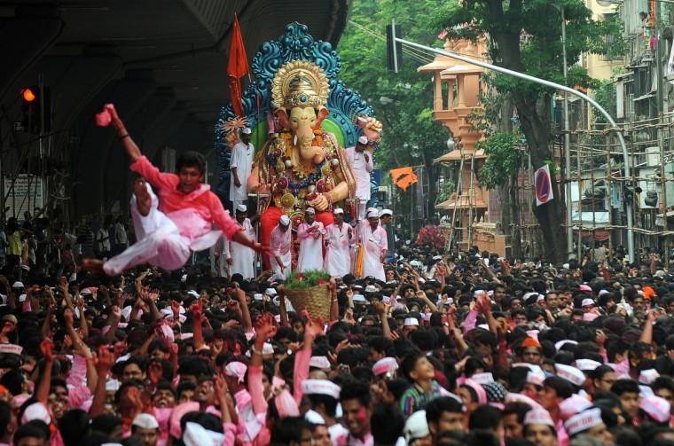 Indian Hindu devotees dance as they take part in a procession for the immersion of a huge idol of the elephant-headed Hindu god Lord Ganesha into the Arabian Sea, on the streets of Mumbai. During the ten-day Ganesh Festival Hindu devotees bring home idols of Lord Ganesha and offer prayers in temporary temples in order to invoke his blessings for wisdom and prosperity, culminating with the immersion of the idols in bodies of water, including the ocean on the tenth day. (Punit Paranjpe/Getty Images)