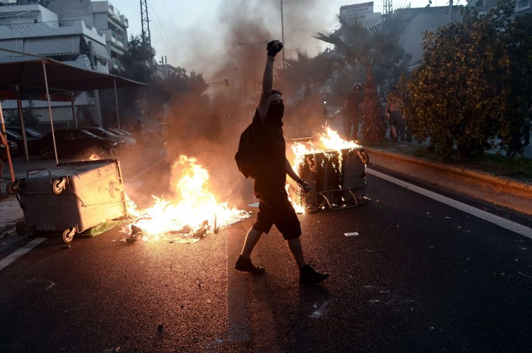 A protestor raises his fist as anti-fascist demonstrators clash with riot police in Athens after a leftist musician was murdered by a suspected neo-Nazi. Pavlos Fyssas, a 34-year-old left-wing hip hop singer, was stabbed to death early today morning outside a Keratsini cafeteria.(Aris Messinis/Getty images)
