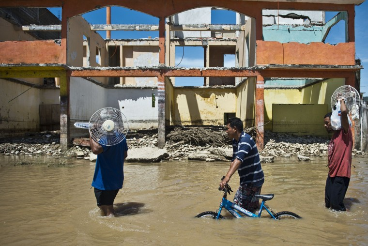 Local residents wade through a flooded street in Acapulco, state of Guerrero, Mexico as heavy rains hit the country. Mexican authorities scrambled to launch an air lift to evacuate tens of thousands of tourists stranded amid floods in the resort of Acapulco following a pair of deadly storms. (Ronaldo Schemidt/Getty images)