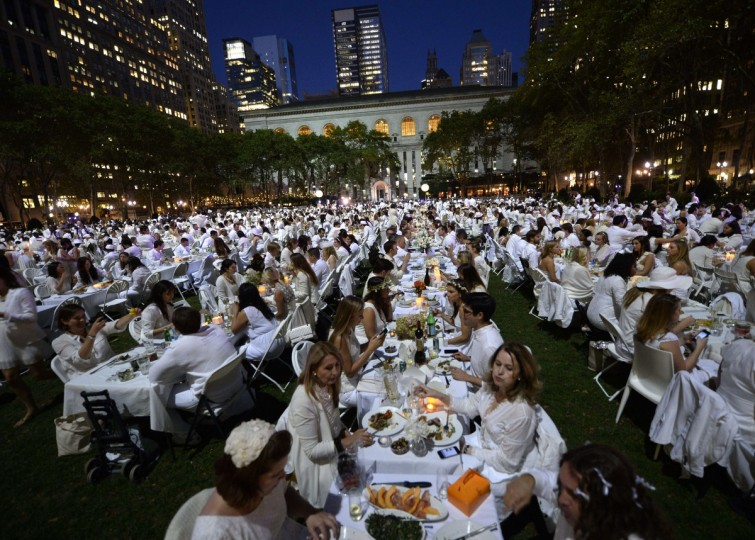 Guests are seated for dinner at Bryant Park during the annual Diner en Blanc, the worlds only viral culinary event, a chic secret pop-up style picnic imported from France. Celebrating its 25th anniversary, the outdoor site -- always a landmark location -- is revealed at the last-minute. Guests are asked to dress entirely in elegant white, bring a picnic basket of food, fine china and silverware, white tablecloths, table and chairs. (Timothy Clary/Getty Images)