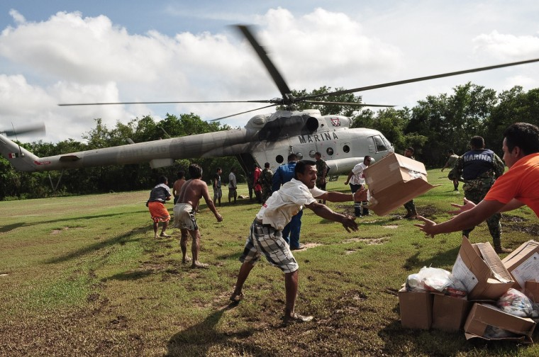 Evacuees unload food boxes from a Mexican Navy helicopter in an area of Acapulco, state of Guerrero, Mexico as heavy rains hit the country. (Claudio Vargas/Getty images)