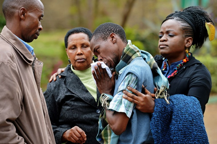 A man only identified by his first name, Stephen (C) is comforted by Pastor Elizabeth Akinyi (R) and family members at the city mortuary in Nairobi on September 23, 2013. Stephen's father was killed in the Westgate mall siege on September 21, 2013. Kenyan Defence troops remain inside the mall, in a standoff with Somali militants after they laid siege to the shopping centre shooting and throwing grenades as they entered. (Carl de Souza/Getty Images)