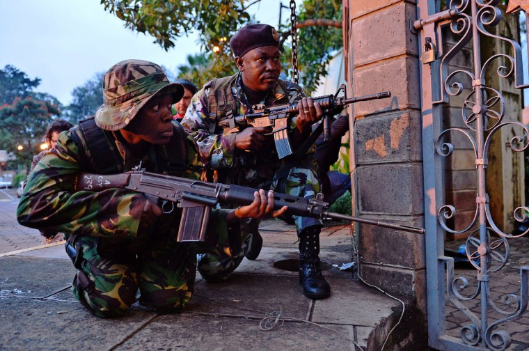 Kenyan soldiers take cover after heavy gunfire near Westgate mall in Nairobi on September 23, 2013. Kenyan Defence troops remain inside the mall, in a standoff with Somali militants after they laid siege to the shopping centre shooting and throwing grenades as they entered. Somali Shebab militants on September 23 threatened to kill hostages they are holding in the Nairobi shopping mall as Kenyan troops move to end their siege. (Carl De Souza/Getty images)