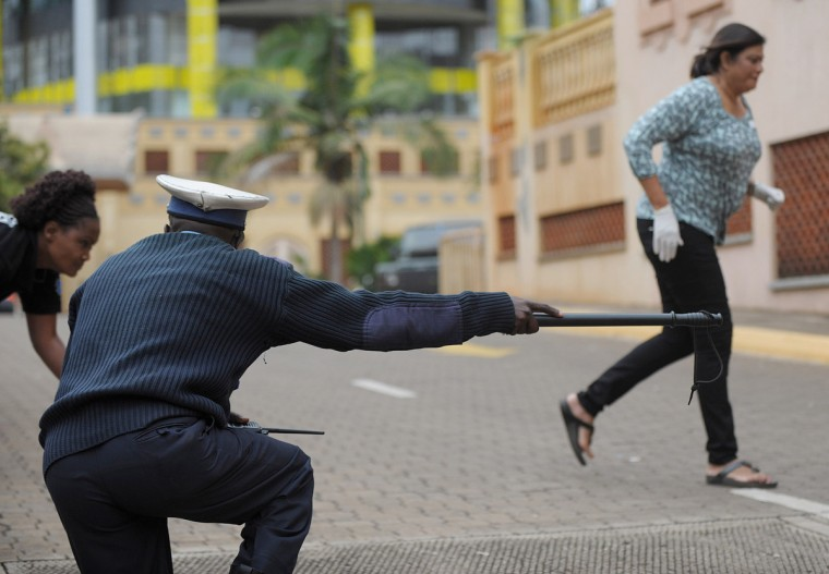 A Kenyan police officer guides volunteers to cover on September 23, 2013 after hearing a volley of gunshots at the scene of a siegeof an upmarket shopping mall by al-shebab, Somalia based al-Qaeda linked terror network. Atleast 69 are confirmed dead and 63 recorded in an ongoing hostile take-over of the prestigious Westgate shopping mall that has been claimed by the shebab whose operatives have been engaged in heavy exchanges with a combined force of Kenya's defence forces an elite police units. (Tony Karumba/Getty images)