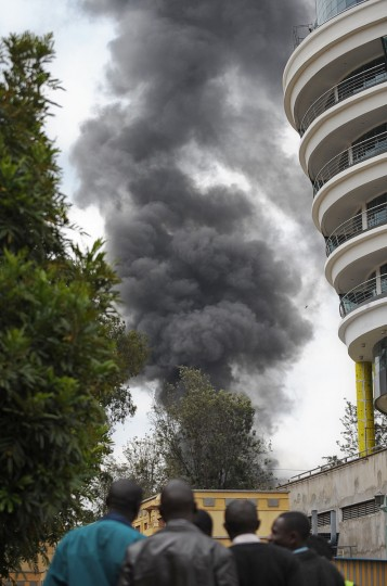 People watch a column of smoke rise on September 23, 2013 in the vicinity of the beseiged Westgate shopping mall in Nairobi following a loud explosion. Kenyan security forces were locked in a fierce, final battle with Somali Islamist gunmen inside the upmarket mall on September 23 as huge explosions and a barrage of heavy gunfire echoed out of the complex. A thick cloud of black smoke billowed out from the Westgate mall as Kenyan officials said the 50-hour-long siege -- which has seen the gunmen massacre at least 62 people and take dozens more hostage -- was close to being resolved. Somalia's Al-Qaeda-linked Shebab insurgents have claimed the attack, which began midday on September 21, when the gunmen marched into the complex, firing grenades and automatic weapons and sending panicked shoppers fleeing. (Tony Karumba/Getty images)