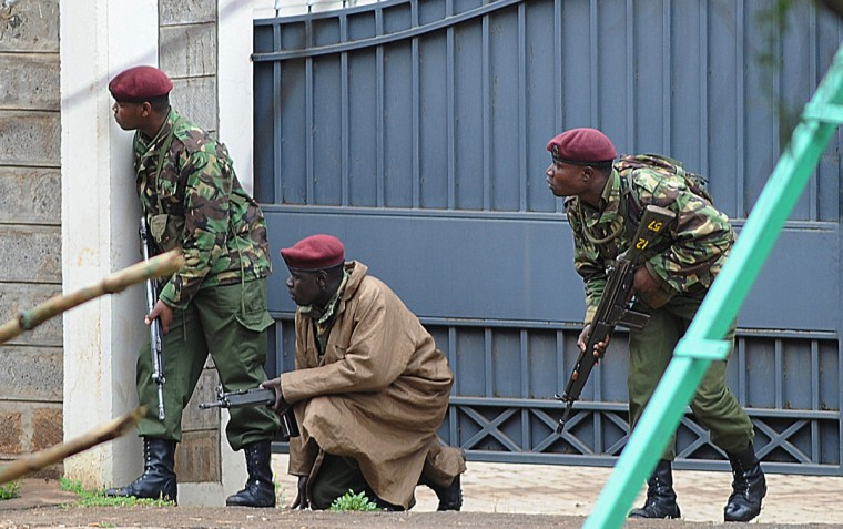 Armed Kenyan policemen take cover outside the Westgate mall in Nairobi on September 23, 2013. Kenyan troops were locked in a fierce firefight with Somali militants inside an upmarket Nairobi shopping mall on September 22 in a final push to end a siege that has left at least 69 dead and 200 wounded with an unknown number of hostages still being held. Somalia's Al Qaeda-inspired Shebab rebels said the carnage at the part Israeli-owned complex mall was in retaliation for Kenya's military intervention in Somalia, where African Union troops are battling the Islamists. (Simon Maina/Getty images)