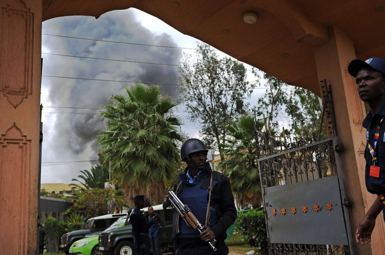 A Kenyan police officer mans on September 23, 2013 the entrance of a building in the vicinity of the beseiged Westgate shopping mall in Nairobi from where a column of smoke rises following a loud explosion. Kenyan security forces were locked in a fierce, final battle with Somali Islamist gunmen inside the upmarket mall on September 23 as huge explosions and a barrage of heavy gunfire echoed out of the complex. A thick cloud of black smoke billowed out from the Westgate mall as Kenyan officials said the 50-hour-long siege -- which has seen the gunmen massacre at least 62 people and take dozens more hostage -- was close to being resolved. Somalia's Al-Qaeda-linked Shebab insurgents have claimed the attack, which began midday on September 21, when the gunmen marched into the complex, firing grenades and automatic weapons and sending panicked shoppers fleeing. (Tony Karumba/Getty images)