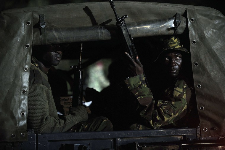 """Kenyan paramilitaries drive towards the Westgate mall in Nairobi. Kenyan President Uhuru Kenyatta announced today that the four-day siege by Islamist gunmen of a Nairobi shopping mall was over, with the """"immense"""" loss of 61 civilians and six members of the security forces. (Simon Maina/Getty Images)"""