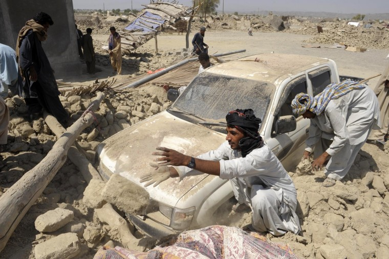 Pakistani survivors clear the debris of destroyed houses in the earthquake-devastated district of Awaran. Desperate villagers in southwest Pakistan clawed through the wreckage of their ruined homes , a day after a huge earthquake struck, killing more than 270 people and creating a new island off the coast. (Banaras Khan/Getty Images)