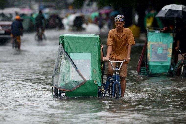 A pedicab driver wades through a flooded street in Manila. (NOEL CELIS / AFP/Getty Images)