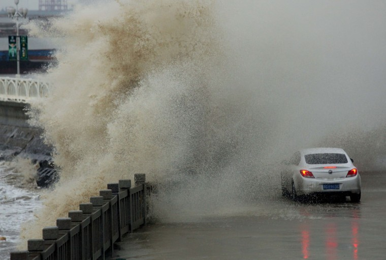 A car is driven along the bank as strong waves hit the coast in Lianyungang, China. (Photo by ChinaFotoPress via Getty Images)