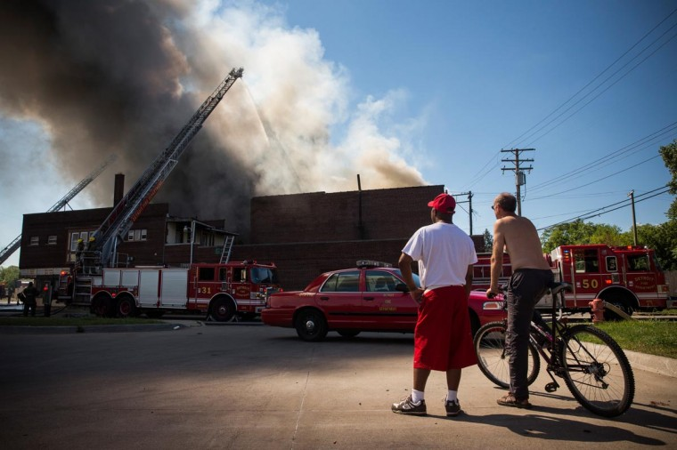 Men watch as members of the Detroit Fire Department fight a two-alarm fire that broke out in an abandoned building on September 4, 2013 in the Six Mile Gratiot neighborhood of Detroit, Michigan. (Andrew Burton/Getty Images)