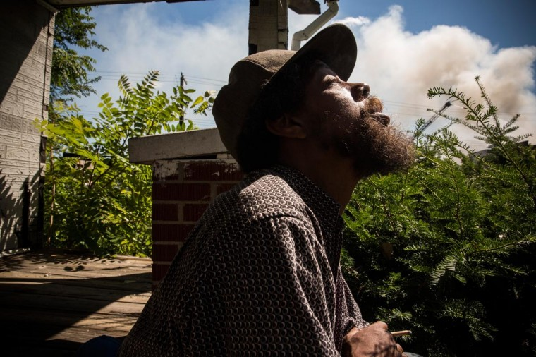 Tony Brown, a homeless man, smokes a cigarette as members of the Detroit Fire Department fight a two-alarm fire that broke out in an abandoned building down the street on September 4, 2013 in the Six Mile Gratiot neighborhood of Detroit, Michigan. (Andrew Burton/Getty Images)