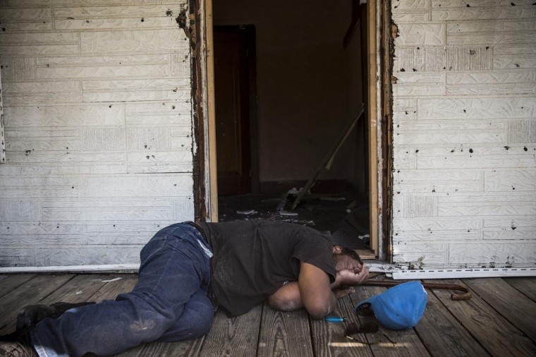 A homeless man takes a nap on the front porch of an abandoned home as members of the Detroit Fire Department fight a two-alarm fire that broke out in an abandoned building down the street on September 4, 2013 in the Six Mile Gratiot neighborhood of Detroit, Michigan. (Andrew Burton/Getty Images)
