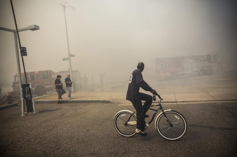 A man rides his bike past as members of the Detroit Fire Department fight a two-alarm fire that broke out in an abandoned building on September 4, 2013 in the Six Mile Gratiot neighborhood of Detroit, Michigan. (Andrew Burton/Getty Images)