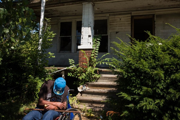 A man sleeps in a wheelchair outside an abandoned home on September 4, 2013 in the Six Mile Gratiot neighborhood of Detroit, Michigan. (Andrew Burton/Getty Images)