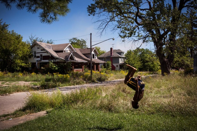 Lawrence Payne practices backflips on his front lawn on September 4, 2013 in the Six Mile Gratiot neighborhood of Detroit, Michigan. (Andrew Burton/Getty Images)
