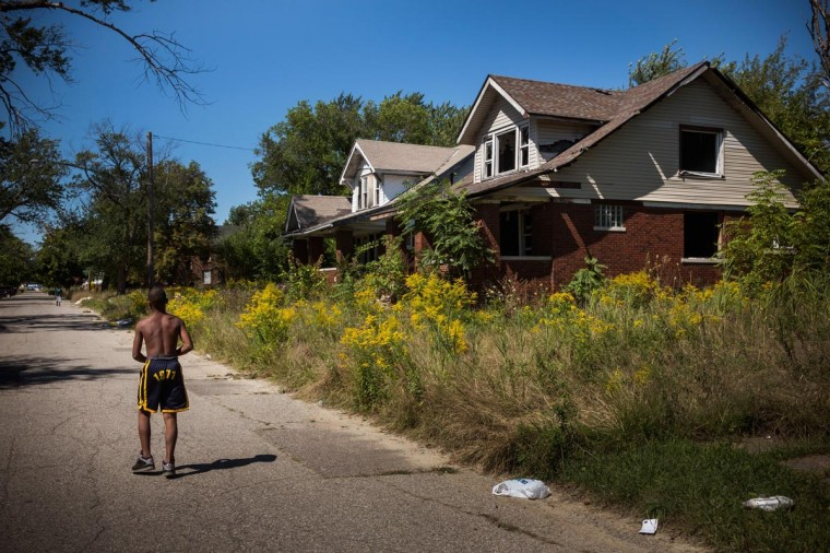 Lawrence Payne walks past two abandoned houses on September 4, 2013 in the Six Mile Gratiot neighborhood of Detroit, Michigan. (Andrew Burton/Getty Images)