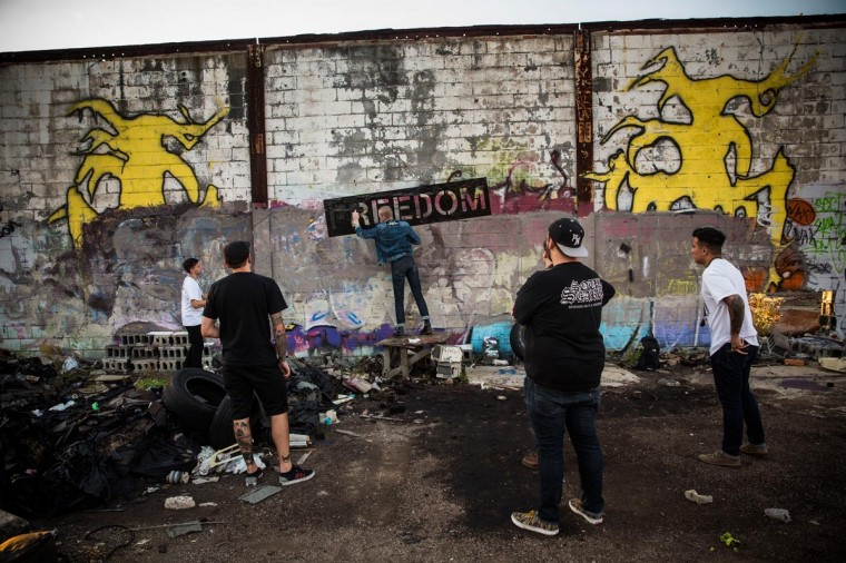 "Members of the band ""Freedom"" spray paint their name on a wall at the abandoned Packard Automotive Plant on September 4, 2013 in Detroit, Michigan. The Packard Plant was a 3.5 million square foot car manufacturing plant built completed in 1911. Major operations ceased in 1958, though the plant was used in a limited capacity until the 1990s, with outer buildings used through the mid 2000s. Since then the buildings have fallen into disrepair - they are now used mostly for graffiti artists and scavengers. (Andrew Burton/Getty Images)"