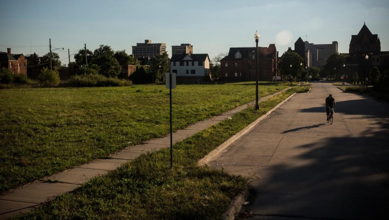 A man rides his bike past empty housing lots on September 5, 2013 in Detroit, Michigan. (Andrew Burton/Getty Images)