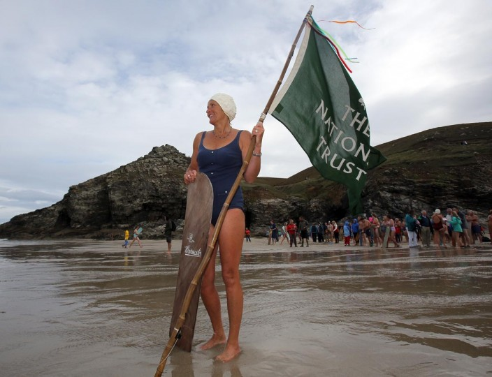 A belly boarder poses for a photograph as she holds a National Trust flag and takes part in the annual World Belly Boarding Championships at Chapel Porth on September 8, 2013 in Cornwall, England. (Matt Cardy/Getty Images)