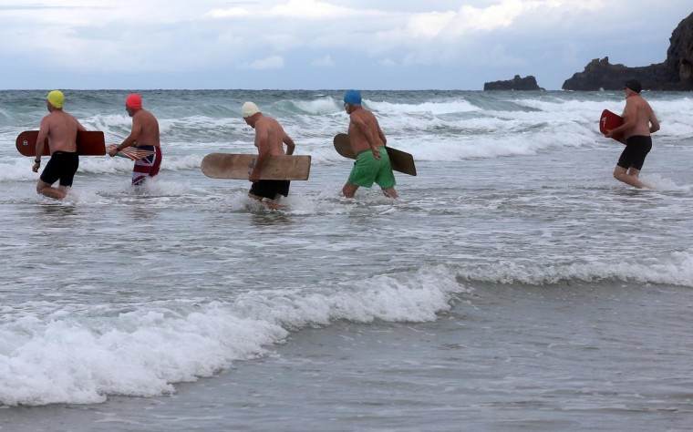 Belly boarders run into the sea to take part in a senior mens heat during the annual World Belly Boarding Championships at Chapel Porth on September 8, 2013 in Cornwall, England. (Matt Cardy/Getty Images)