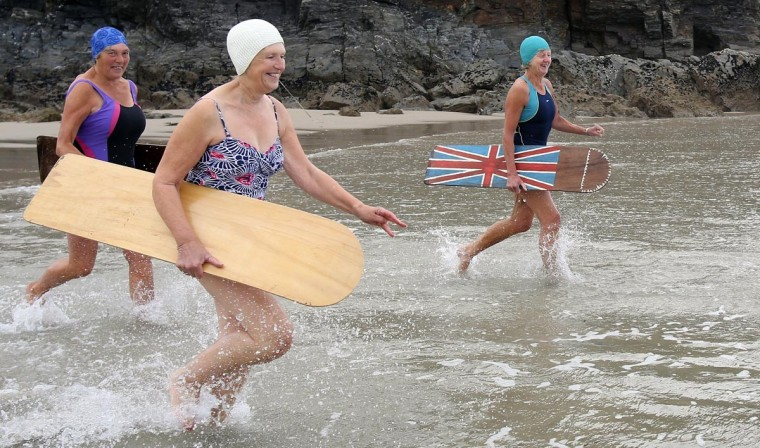 Belly boarders run into the sea to take part in a senior ladies heat during the annual World Belly Boarding Championships at Chapel Porth on September 8, 2013 in Cornwall, England. (Matt Cardy/Getty Images)