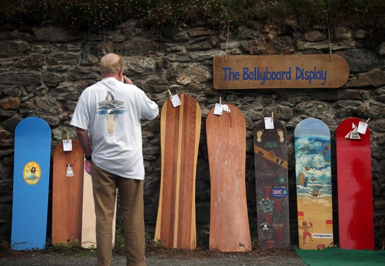 A man looks at vintage bellyboards displayed at the annual World Belly Boarding Championships at Chapel Porth on September 8, 2013 in Cornwall, England. (Matt Cardy/Getty Images)
